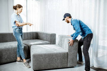Delivery man mounting new sofa for a young woman client in the modern apartment