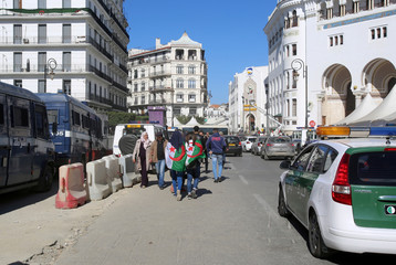 People wear Algerian national flags as they walk past police vehicles in Algiers