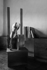 Black and white still life shot of broken old broken violin and vintage grunge books