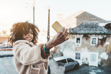 A skittish young curly-hair African-American female in a winter coat issmiling and taking a selfie using her smartphone while standing outdoors on an antique street of a European city on a spring day