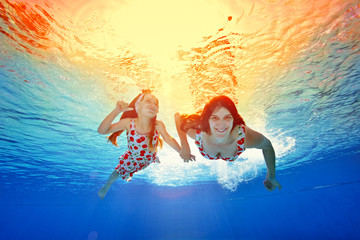 Happy mother and daughter swim under the water holding hands against the bright orange sunset in the same dresses. Portrait. Shooting underwater. Horizontal orientation of the image
