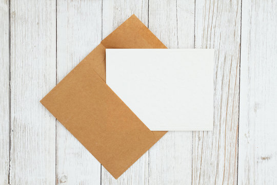 Blank envelope with greeting card on weathered whitewash textured wood background
