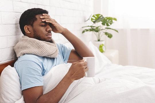 Sick african-american man drinking hot healing tea in bed