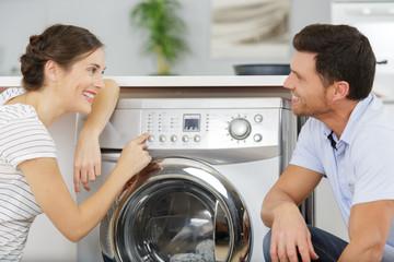 smiling couple next to the washing machine