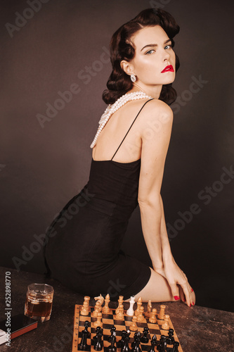 c0d46ac601 Retro brunette girl playing chess. Slim tan woman in sexy dress with red  nails. Chess board with glass of whiskey. Gorgeous brunette lady with red  lips and ...