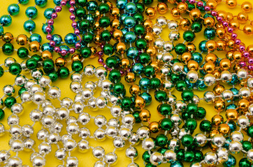 Mardi Gras beads on yellow background. Close up photo of mardi gras beads