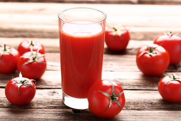 Wall Mural - Tomato juice in glass on brown wooden table