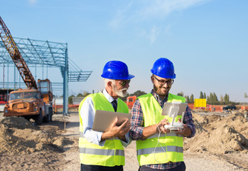 Construction engineers with drone at building site
