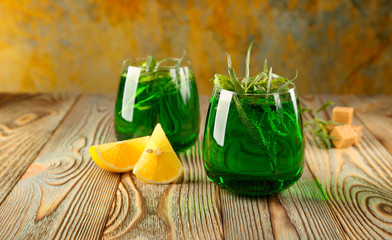 Sparkling tarragon (estragon) water in a glass, with sprigs of tarragon.