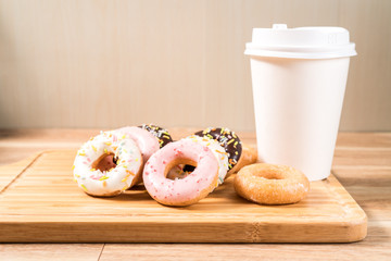 Donuts and coffee on wooden table.