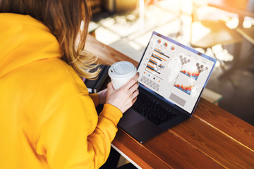 Close-up view of laptop screen with graphs,diagrams on monitor.Girl in yellow hoodie works on computer in cafe.Marketing
