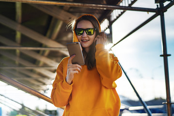 Smiling woman in casual clothes using smartphone while standing on street. Girl using application for tourists, dating.