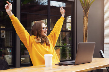 Girl rejoices in winning having raised her hands up sitting in front of laptop.Woman watches sports match on computer.
