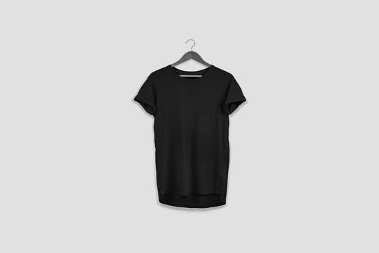 Blank black T-Shirt Mock-up hanging on white wall, front side view. Ready to replace your design.