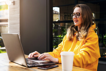 Girl in yellow hoodie sits in cafe in front of open laptop computer. Woman works on computer, checks email. Marketing.