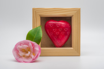 Square wooden frame mockup with a single pink flower with a green leaf placed at a corner of the photo frame. A red heart stone sits inside of the frame.