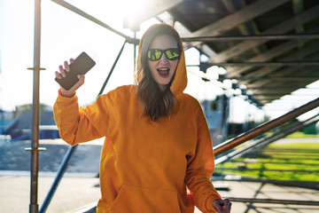 Young woman in yellow hoodie is shocked by read message on mobile phone. Girl enjoys receiving good news in e-mail on smartphone.