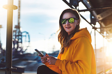 Smiling woman in yellow hoodie using smartphone on street. Girl in casual wear and sunglasses writes text message on phone.