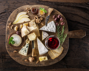 Cheese platter with organic cheeses, fruits, nuts and wine on wooden background. Top view. Tasty cheese starter.