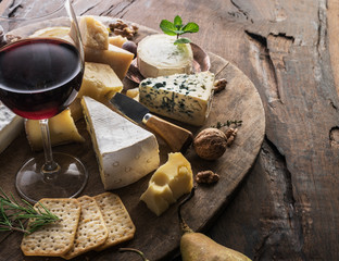 Wall Mural - Cheese platter with organic cheeses, fruits, nuts and wine on wooden background. Tasty cheese starter.