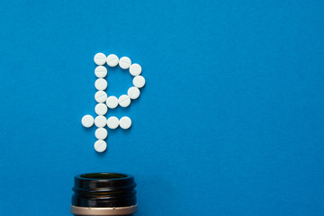 white pills in the shape of a ruble are scattered on a blue background next to a dark bottle.