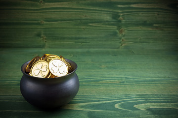 gold coins in caldron for st. patricks day on green wooden background