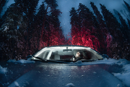 A car with a driver in a winter pine forest. Night time