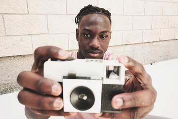 Young man holding an old analog camera