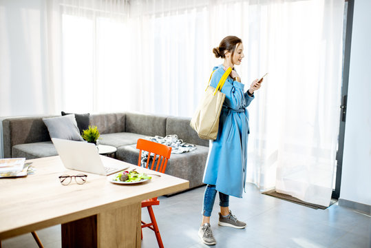 Young stylish woman in the coat standing with phone and bag in the modern apartment ready to leave