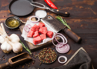 Raw lean diced casserole beef pork steak with vintage meat hatchet and fork on wooden background. Salt and pepper with fresh rosemary, red onion and garlic with rosemary.