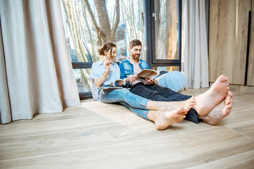 Happy couple sitting together on the floor near the window with beautiful view, reading some magazines and relaxing at home