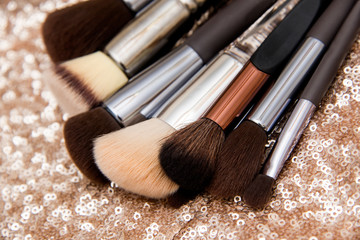 Professional makeup brushes on pink sequin background