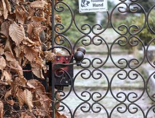Gartentor mit Schild 'Freilaufender Hund - Tor bitte geschlossen halten'