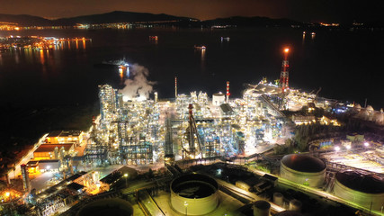 Aerial drone night shot of industrial oil refinery plant with dazzling lights