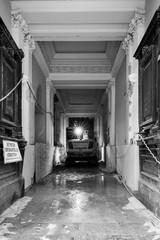 Bagger auf Baustelle in altem Haus. Digger in old dark building on construction site.