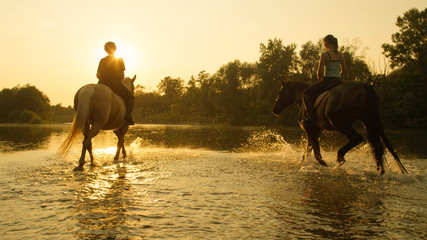 LENS FLARE: Active girls riding their strong horses down the river shallows. Wall mural