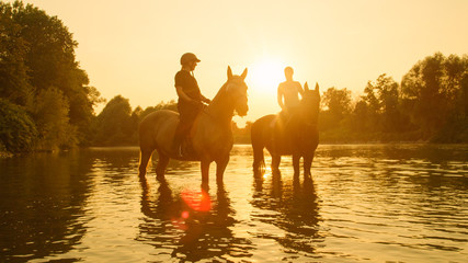 SILHOUETTE: Horseback riders stop their horses while riding them along a stream.