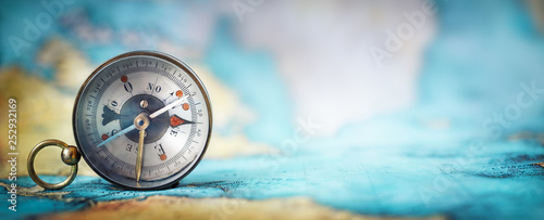 Wall mural Magnetic old compass on world map.Travel, geography, navigation, tourism and exploration concept wide background. Macro photo. Very shallow focus.