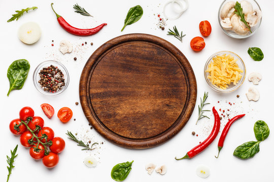 Round cutting board with pizza ingridients around
