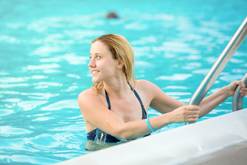 Young attractive girl in the swimming pool at day