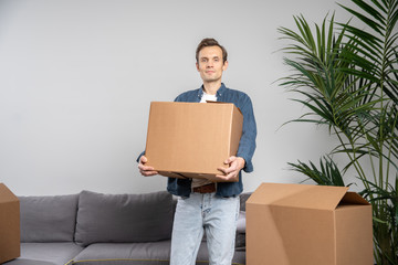 Man with cardboard box in hands standing in apartment.