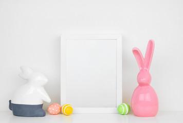 Mock up white frame with Easter Eggs and modern Easter bunny decor on a shelf or desk. Easter concept. White color scheme. Portrait frame orientation.