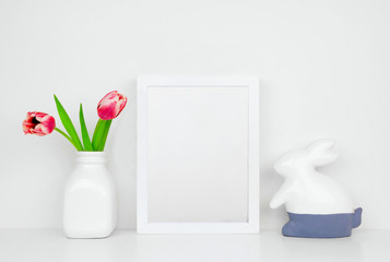 Mock up white frame with tulip flowers and modern bunny decor on a shelf or desk. Easter concept. White color scheme. Portrait frame orientation.