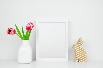 Mock up white frame with tulip flowers and modern wood bunny decor on a shelf or desk. Easter concept. White color scheme. Portrait frame orientation.