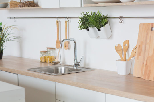 White kitchen Interior in scandinavian style with kitchenware and green plants