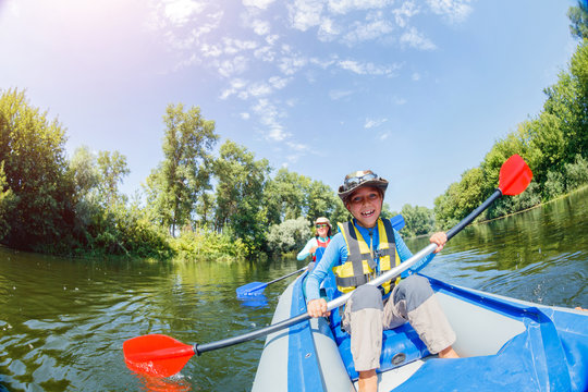 Happy boy kayaking on the river on a sunny day during summer vacation