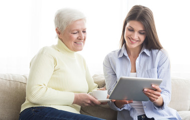 Senior mother and daughter browsing internet on tablet
