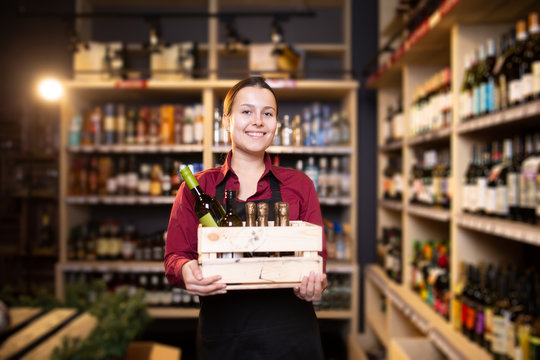 Image of happy brunette seller with wooden box with wine in store