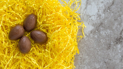 four chocolate Easter eggs nestled in yellow Easter grass on a gray marble counter with copy space