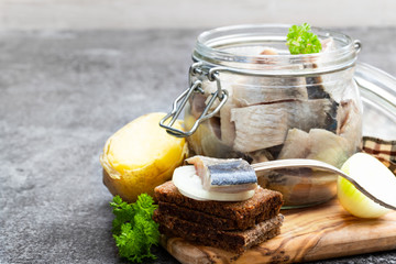 Homemade marinated herring in glass jar with rye bread and jacket potato on gray table